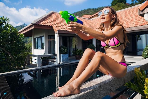 Довольно улыбающаяся счастливая женщина играет с игрушкой из водяного пистолета в бассейне на летних тропических каникулах на вилле, развлекаясь в купальнике бикини, красочном стиле, праздничном настроении Бесплатные Фотографии