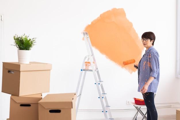 페인트 롤러와 집의 인테리어 벽 그림 꽤 웃는 중년 여성. 프리미엄 사진