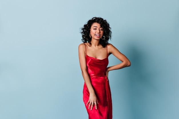 Довольно улыбается женщина в красном платье, глядя на фронт Бесплатные Фотографии