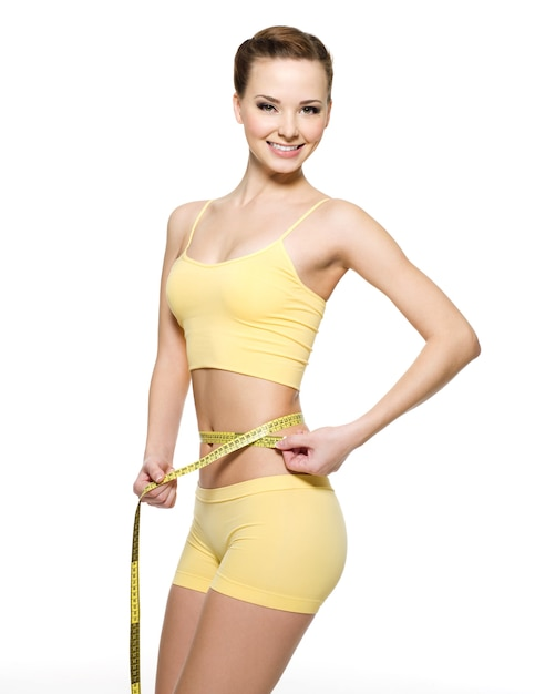 Pretty smiling woman measuring waist with  measurement type isolated on white Free Photo