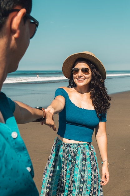Pretty smiling woman pulling man to beach Free Photo
