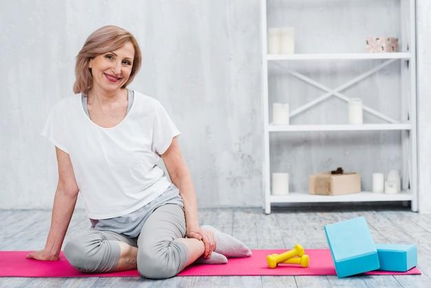 Pretty smiling woman sitting near blocks and dumbbells on yoga mat Free Photo