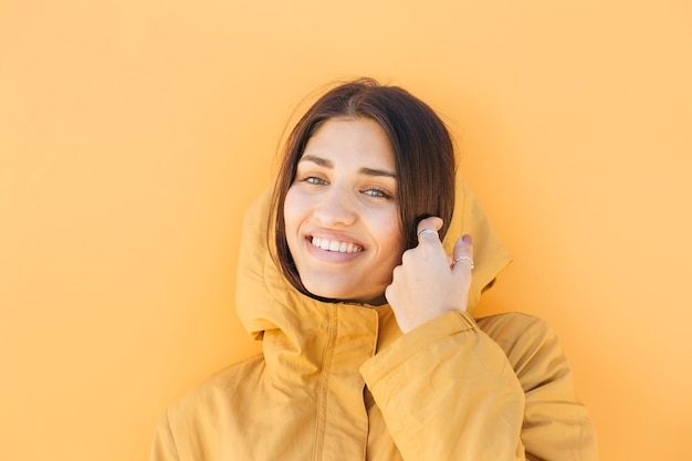 Pretty smiling woman wearing yellow hoodie jacket looking at camera Free Photo