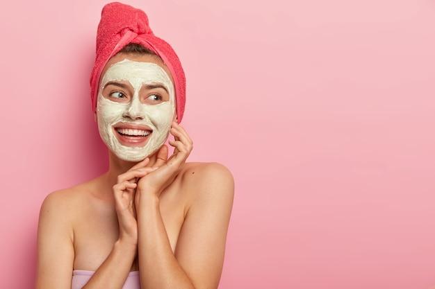 Bella donna sorridente con maschera all'argilla, fa un passo di bellezza, pulisce il viso, indossa un asciugamano avvolto sulla testa, sta a torso nudo, ottiene piacere, riduce i brufoli, copia l'area dello spazio contro il muro rosa Foto Gratuite