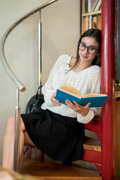 Pretty student with book sitting on stairs Free Photo