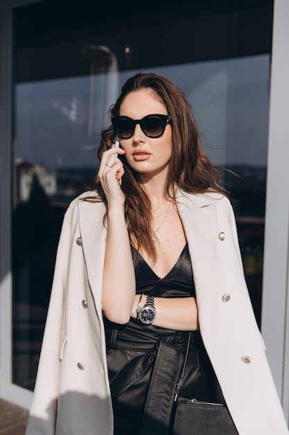 Pretty stylish business woman stands on the balcony near modern office and talking on the smartphone. Premium Photo