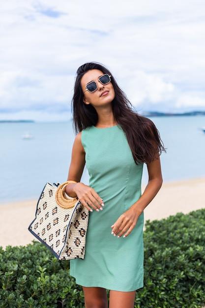 가방 녹색 여름 드레스에 꽤 세련 된 행복 한 여자, 휴가에 선글라스를 착용, 배경에 푸른 바다 무료 사진