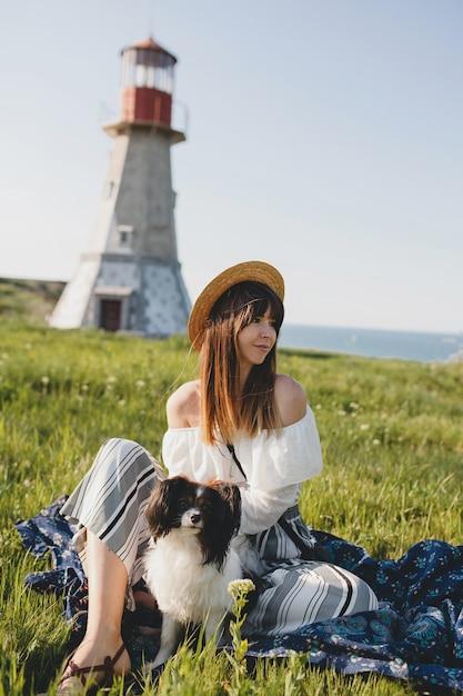 田舎のかなりスタイリッシュな女性、犬、幸せな前向きな気分、夏、麦わら帽子、ボヘミアンスタイルの衣装を保持 無料写真