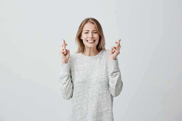 Pretty supertitious young woman with dyed hair in loose sweater crosses fingers, prays before important event, wishes luck, hopes for victory and success. woman feeling hopeful, waiting for miracle Free Photo
