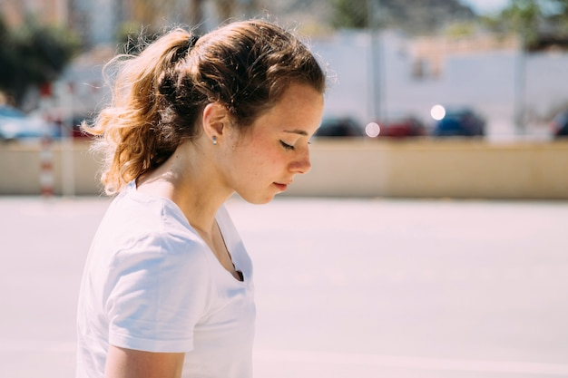 Pretty teen girl looking down in street Free Photo