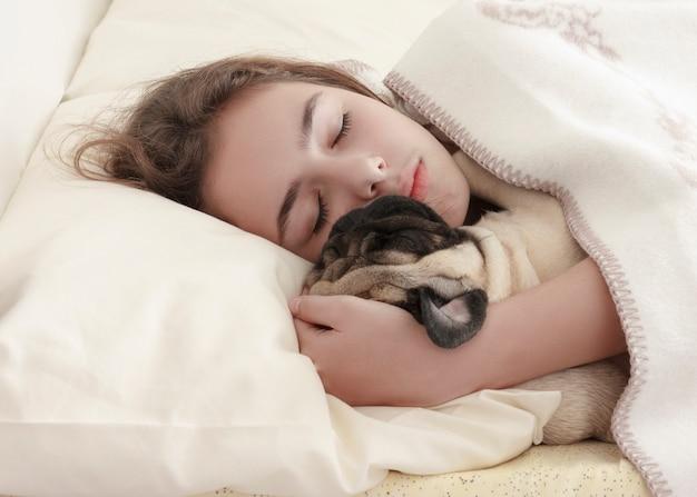 Pretty teen girl sleeps hugging a pug dog in bed Premium Photo