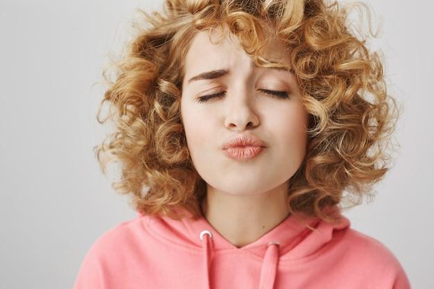 Симпатичная девочка-подросток с вьющимися волосами закрывает глаза и ждет поцелуя Бесплатные Фотографии