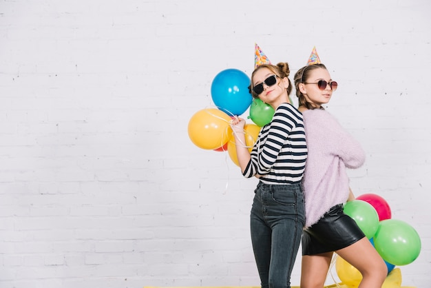 Pretty teenage girls standing back to back holding colorful balloons in hand Free Photo
