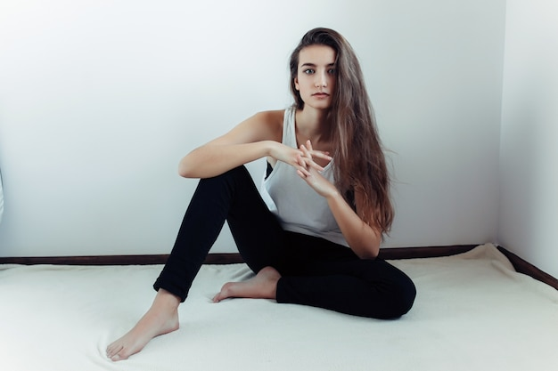 Pretty teenager sitting on the floor