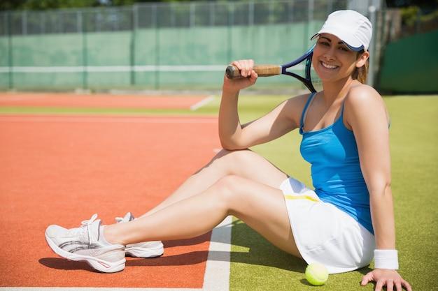 Pretty tennis player sitting on court smiling at camera Premium Photo