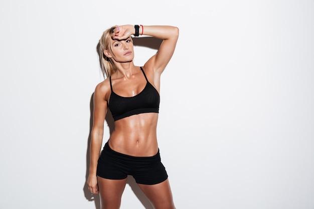 Довольно уставшая спортсменка позирует стоя Бесплатные Фотографии
