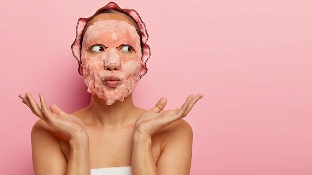 시트 비누 페이셜 마스크를 쓴 꽤 알지 못하는 여성, 아름다움에 대한 관심, 건강한 피부를 갖고 싶어, 손바닥을 어깨 너머로 옆으로 펼칩니다. 무료 사진