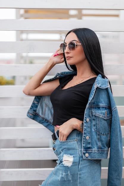 Довольно городская фотомодель молодой женщины с роскошными черными волосами в модной синей джинсовой одежде в стильных темных солнцезащитных очках позирует на открытом воздухе возле белой деревянной стены. девушка красивая битник в городе. Premium Фотографии