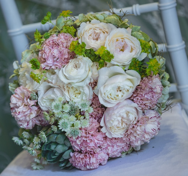 Pretty wedding bouquet of white and pink flowers standing on a white chair Free Photo