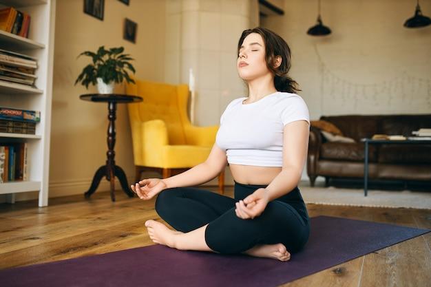 ぽっちゃりした頬を足を組んでヨガマットに座り、目を閉じ、深呼吸をし、瞑想を実践し、心の平安と調和を求めてきれいになります。 無料写真