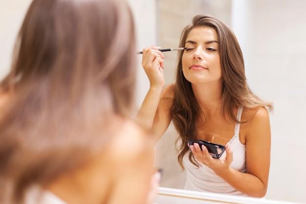 Красивая женщина, применяя тени для век перед зеркалом Бесплатные Фотографии
