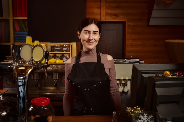 Pretty woman barista in apron behind the bar in a wooden cafeteria Premium Photo