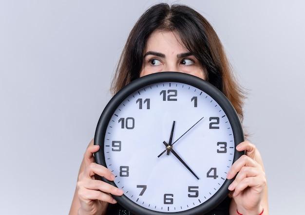 Bella donna in camicetta nera che si nasconde dietro l'orologio che guarda oltre Foto Gratuite