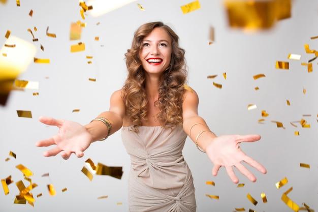 金色の紙吹雪で新年を祝うきれいな女性 無料写真