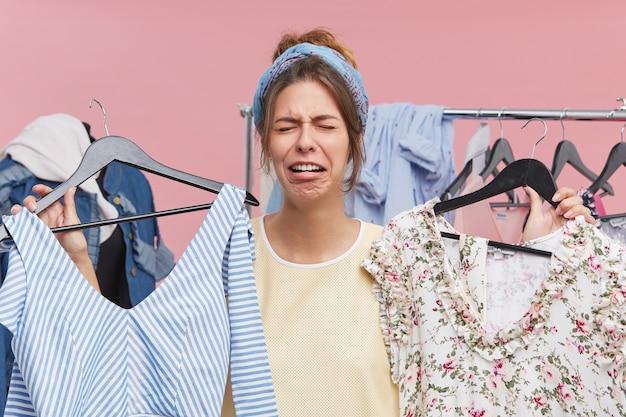 Красавица плачет, стоя в гардеробе, держа в руках два модных платья высокой цены, не имея денег на их покупку. расстроенная, несчастная женщина не может найти что-то подходящее для себя Бесплатные Фотографии