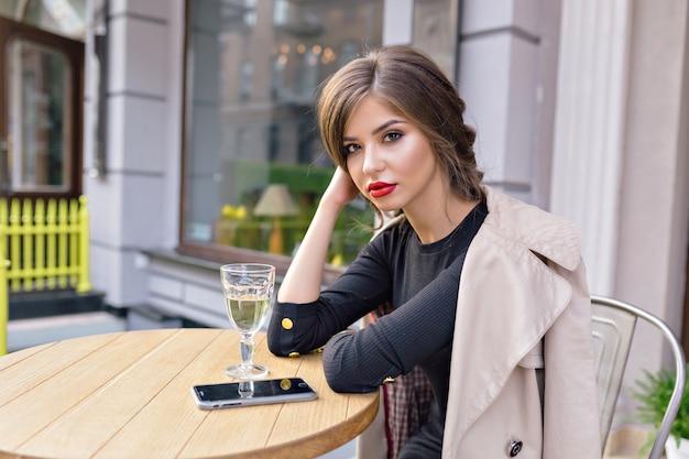 Bella donna vestita in abito nero e trench beige con acconciatura alla moda e labbra rosse su una terrazza Foto Gratuite