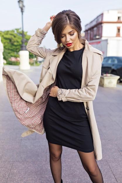 通りでスタイリッシュな髪型と赤い唇と黒のドレスとベージュのトレンチに身を包んだきれいな女性 無料写真