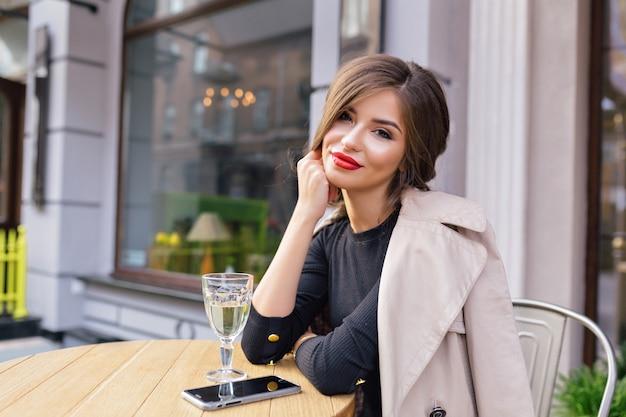 テラスでスタイリッシュな髪型と赤い唇と黒のドレスとベージュのトレンチに身を包んだきれいな女性 無料写真