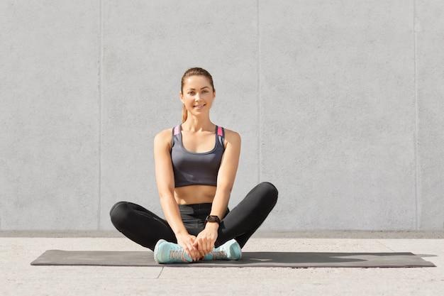 きれいな女性は定期的にスポーツに行く、スポーツウェアに身を包んだ、ジムでマットの上に組んだ足を座っている、ヨガの練習の後に休憩している 無料写真