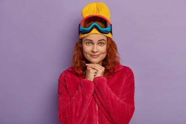 예쁜 여자는 손을 모으고 노란색 모자와 빨간 코트를 입고 카메라를 직접보고 뺨에 보조개가 있습니다. 활동적인 스키어 무료 사진