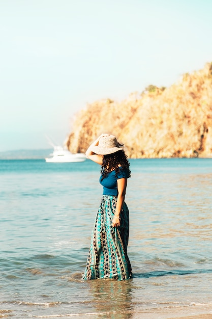Pretty woman in hat standing in coastal wave on beach Free Photo