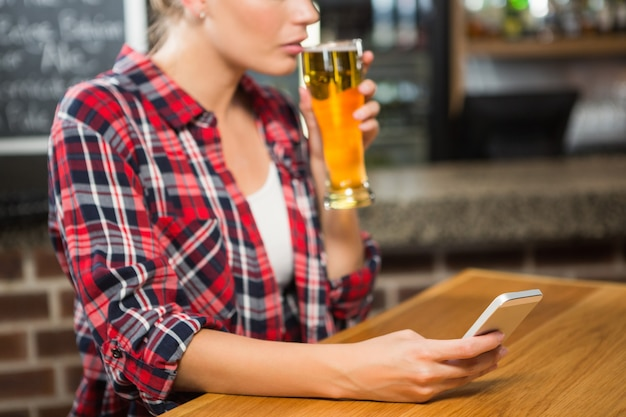 Pretty woman having a beer and looking at smartphone Premium Photo