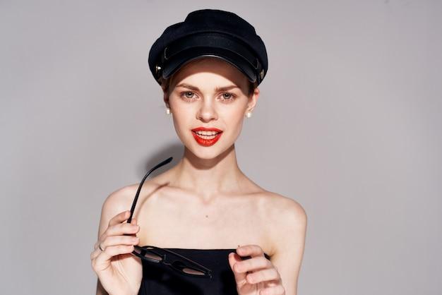 화장품 매력의 손에 선글라스와 검은 드레스에 예쁜 여자보기를 잘립니다. 프리미엄 사진
