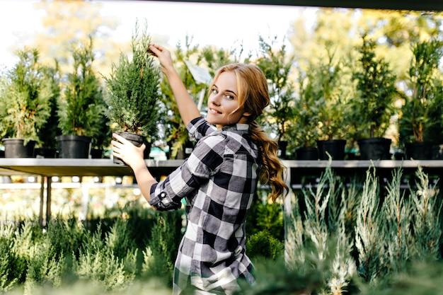 Красивая женщина в милой одежде тянется к растениям в теплице Бесплатные Фотографии