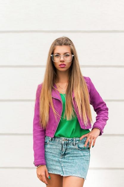 Красивая женщина в модных солнцезащитных очках и розовой куртке Premium Фотографии