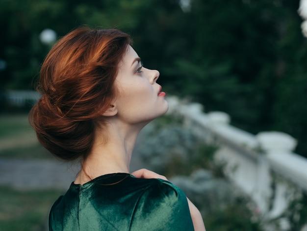 緑のドレスを着たきれいな女性が屋外で魅力的な外観の豪華さ。高品質の写真 Premium写真