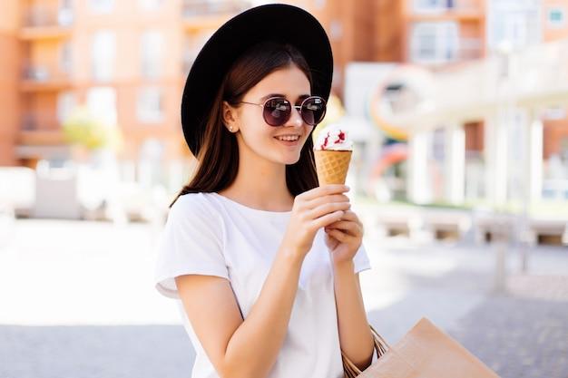 帽子とサングラスの買い物袋と街の通りで話しているアイスクリームのきれいな女性 無料写真