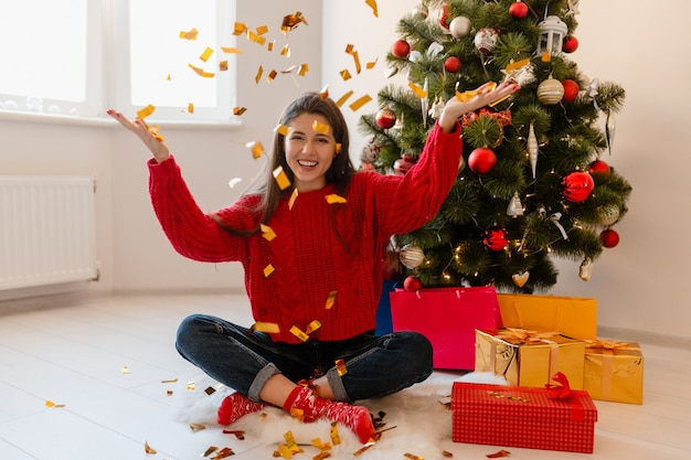 Красивая женщина в красном свитере сидит дома у елки, бросая золотое конфетти в окружении подарков и подарочных коробок Бесплатные Фотографии