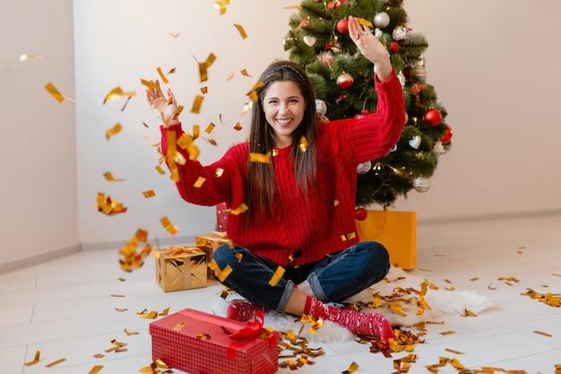 선물 및 선물 상자에 둘러싸인 황금 색종이를 던지고 크리스마스 트리에서 집에 앉아 빨간 스웨터에 예쁜 여자 무료 사진