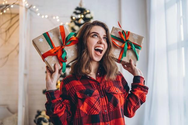 クリスマスのギフトボックスと家で歩くシャツと靴下のきれいな女性 Premium写真