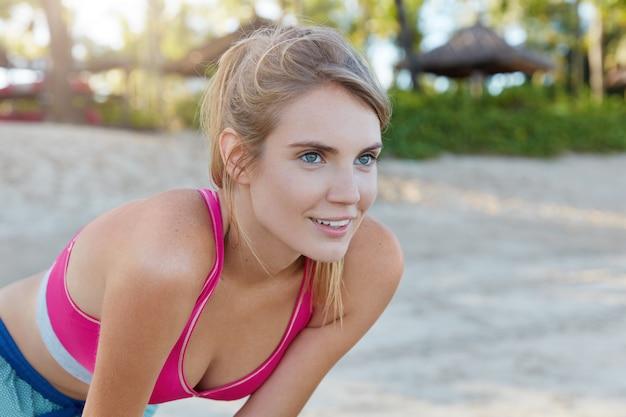 ビーチでスポーツウェアのきれいな女性 無料写真
