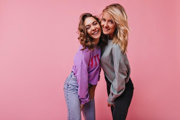 妹と笑っているヴィンテージジーンズのきれいな女性。笑顔でピンクの上に立っている陽気な女の子の屋内の肖像画。 無料写真