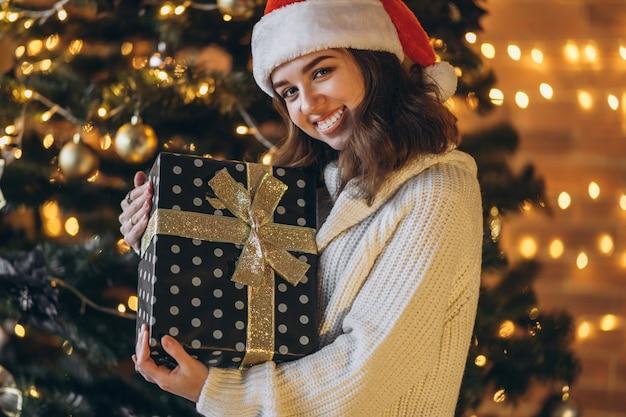 暖かいセーターとクリスマス帽子のきれいな女性、gifボックスを保持しています Premium写真