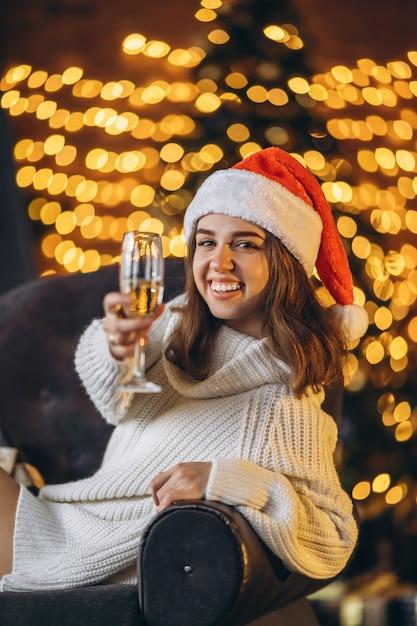 暖かいセーター、靴下、クリスマス帽子のきれいな女性、シャンパンで椅子に座って Premium写真