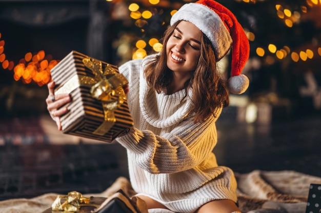 床に座って、暖かいセーター、靴下、クリスマス帽子のきれいな女性 Premium写真