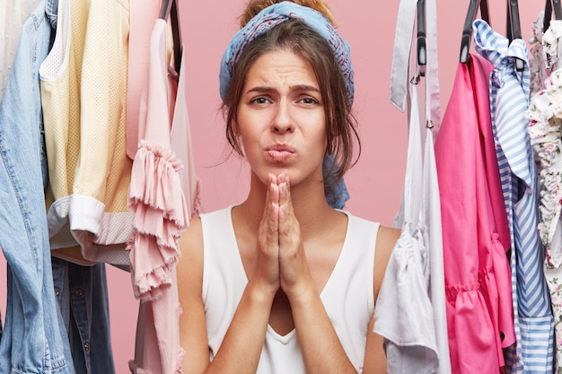 Pretty woman keeping hands together looking with sorrorful expression, standing near her wardrobe, complaining that she has no dresses Free Photo